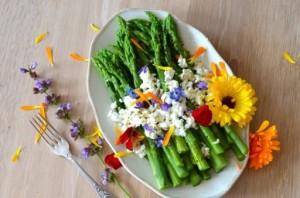 Groene asperges met geitenkaas, eetbare bloemen en vinaigrette van sinaasappel